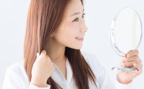 鏡の中の自分を褒める女性